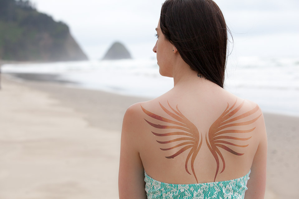 Young woman on beach with wings - Photos By Orion
