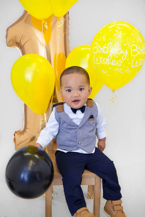 1st birthday photo on a chair with balloons - Photos By Orion